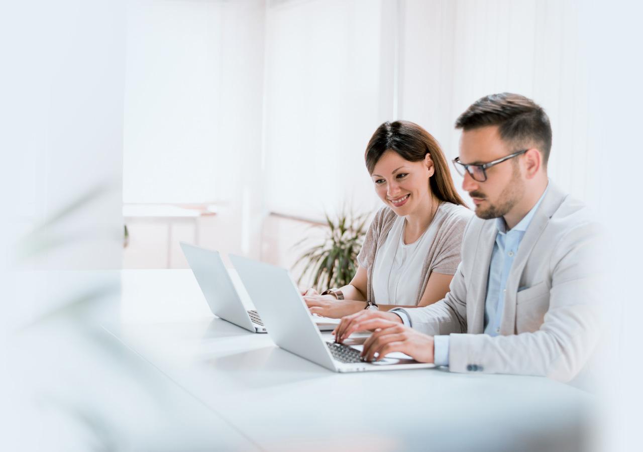 Mann und Frau arbeiten gemeinsam an ihren Notebooks